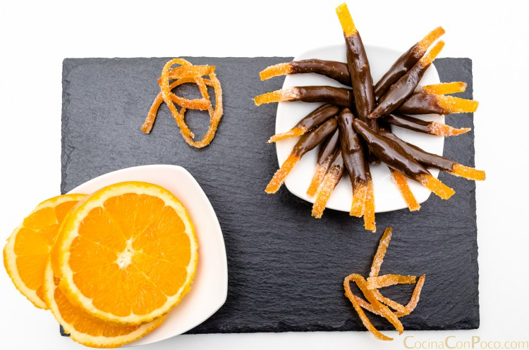 Base de pizarra y encima platos blancos uno con naranja laminaday otro con piel de naranja con chocolate