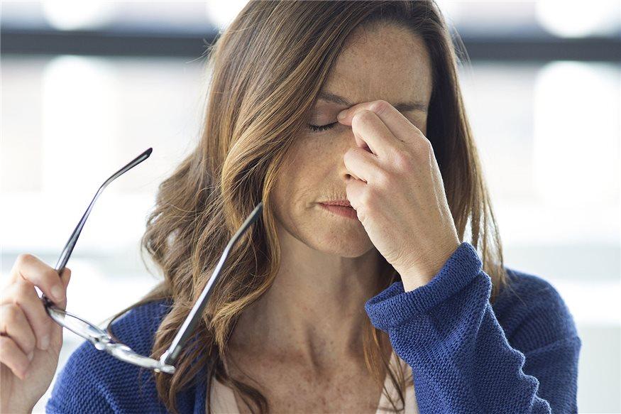 Mujer sujentando las gafas en la mano y tocandose los ojos con gesto de dolor