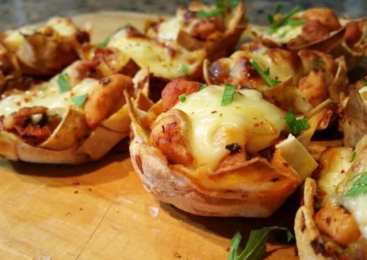 Tartaletas de pollo, queso y tomate sobre tabla de madera