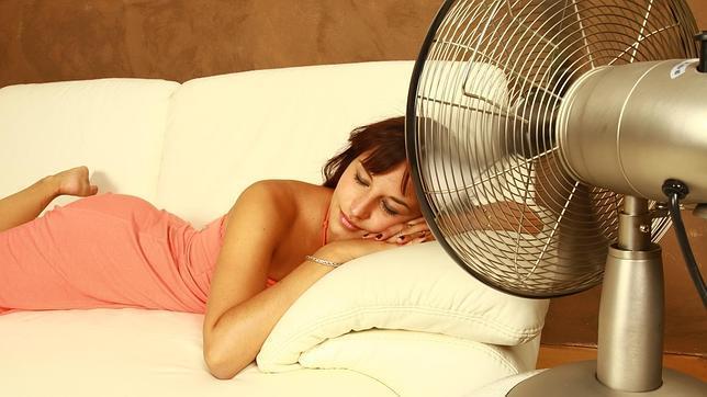 Mujer tumbada en sofa blanco delante de un ventilador