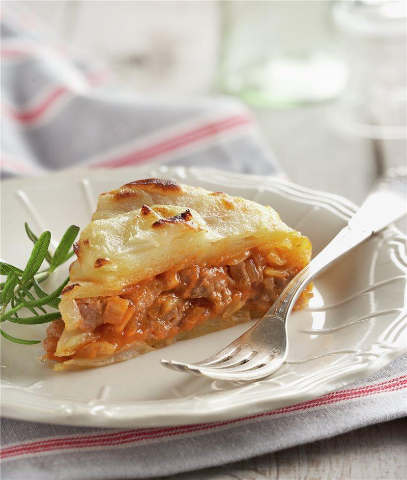 Plato blanco sonre mesa con mantel blanco con Pastel de patata, tomate y lomo de cerdo