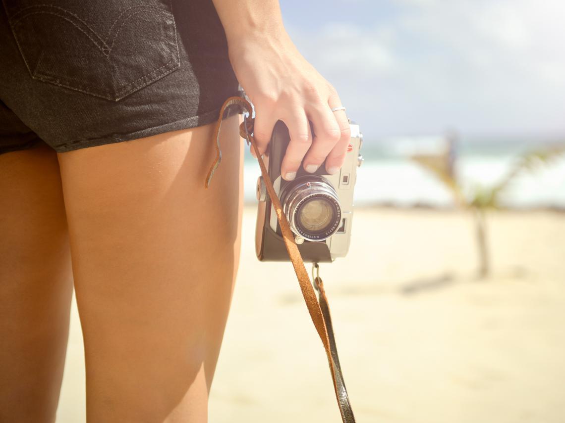 Mujer con short negro frente a una playa con cámara de fotos en la mano