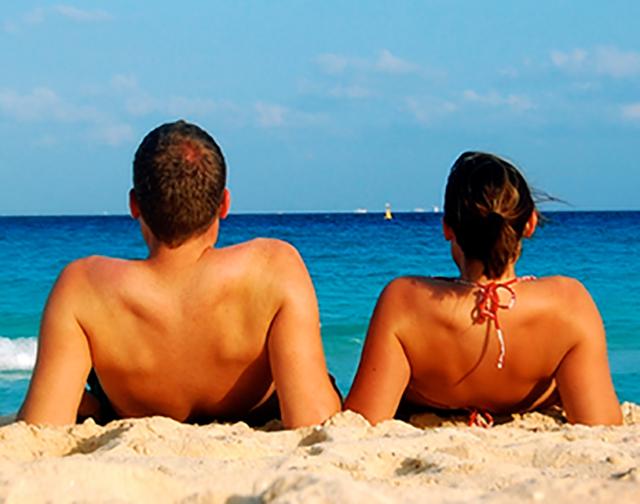 Chico y chica en la playa tomando el sol