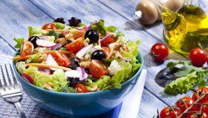 Bol azul con ensalada variada sobre mesa de madera