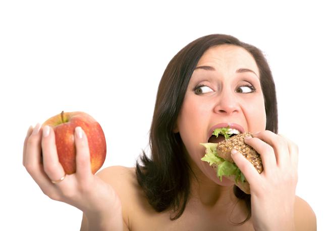 Mujer comiéndose una hamburguesa y dudando si comerse una manzana