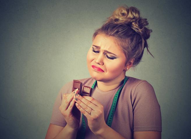 Mujer que con tristeza mira una onza de chocolate
