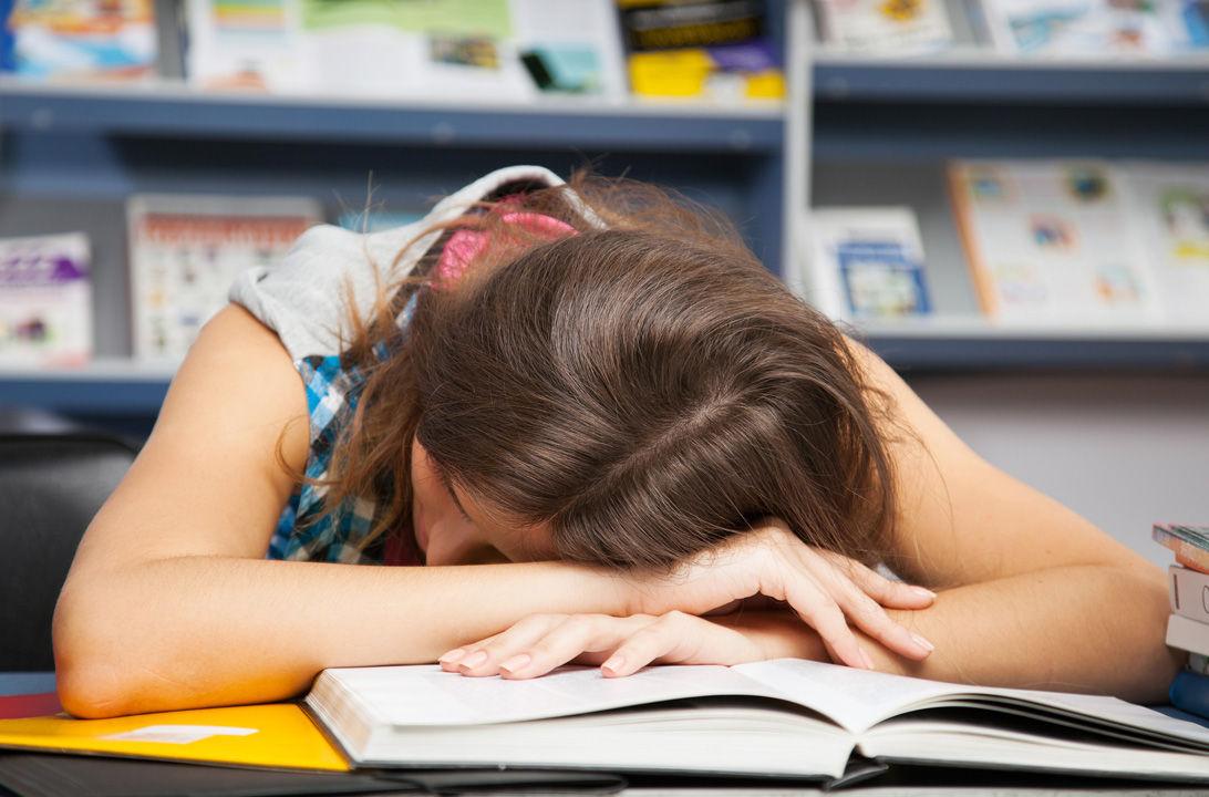 Mujer encima de libros tumbada agotada