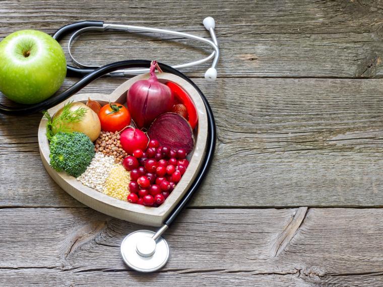 Mesa de madera y encima estetoscopio con alimentos saludables para el corazón