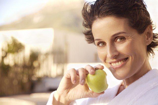 Mujer madura sonriendo con manzana en la mano