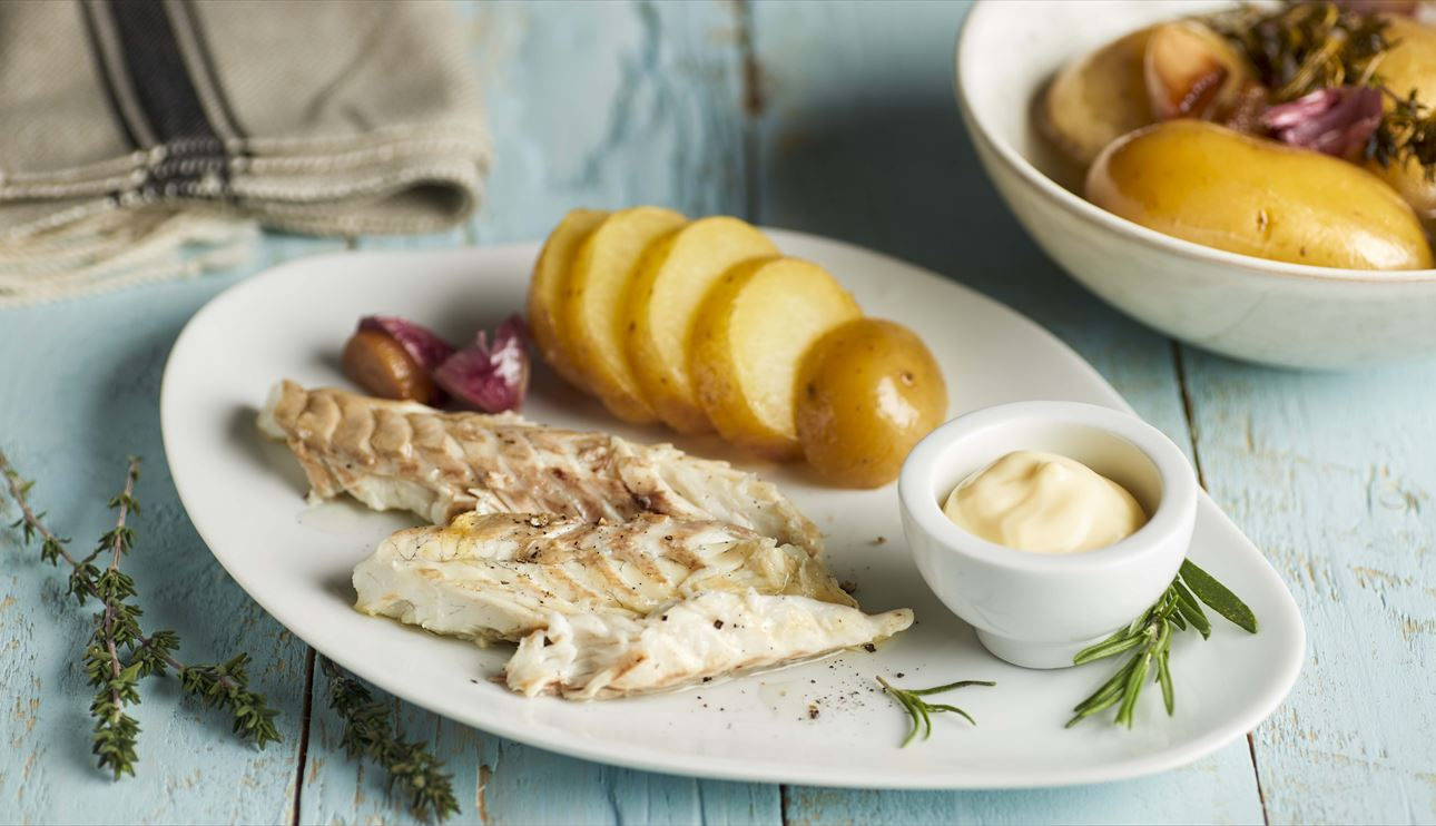 Lubina a la sal en plato blanco con guarnición de ajos y patatas