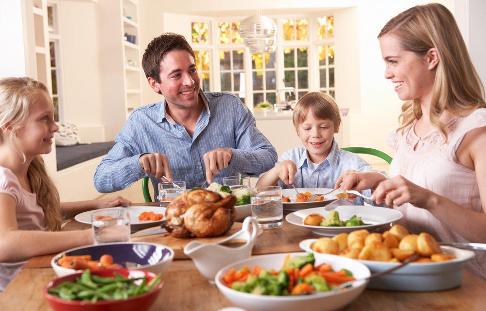 Familia comiendo feliz sobre mesa de madera
