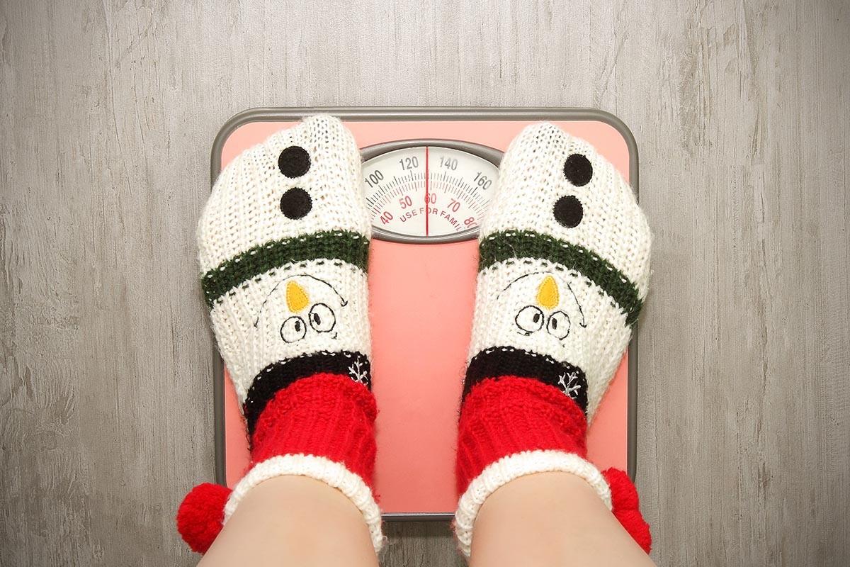 Mujer con calcetines navideños sobre báscula