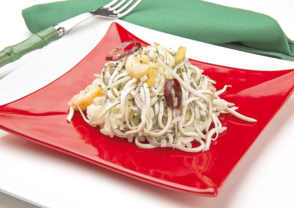 Plato rojo sobre sobreplato blanco con arroz con gulas y gambas