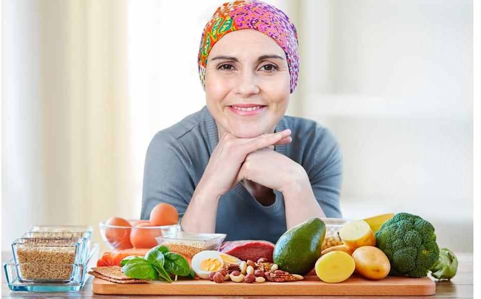 Mujer con tratamiento de cáncer con un montón de aliemtnos sanos sobre tabla de madera