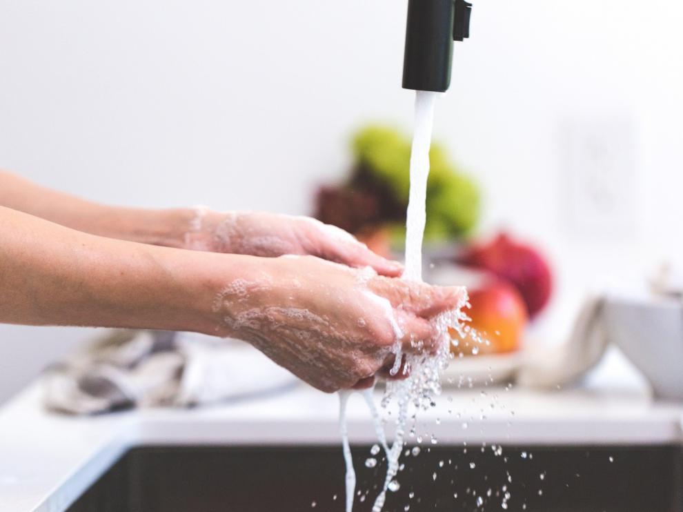 Limpieza de manos en grifo de cocina con alimentos al fondo