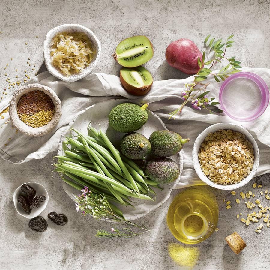 Mantel blanco y sobre él alimentos protectores de salud como aguacate, kiwis, aceite de oliva...