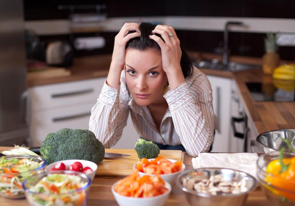 Mujer con cara de angustia sobre mesa de cocina con muchos alimentos