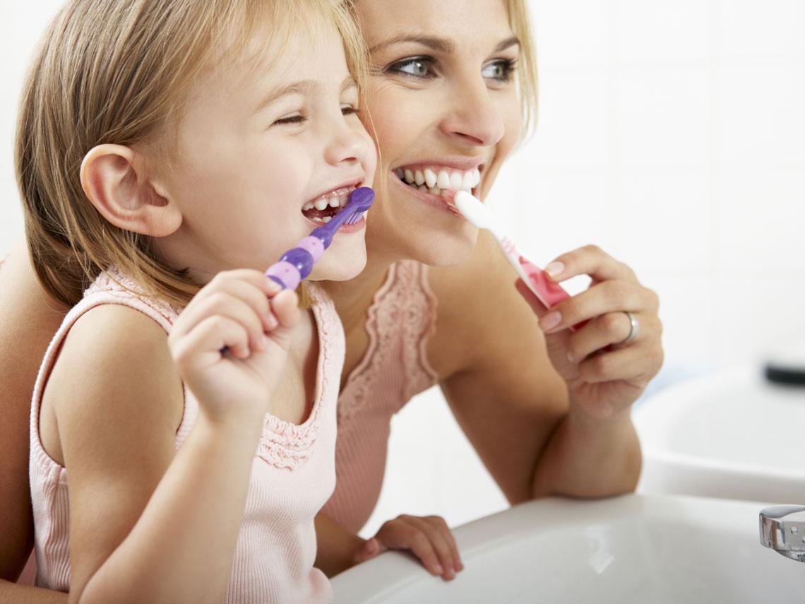 Mujer y niña pequeña frente al espejo ambas lavándose los dientes