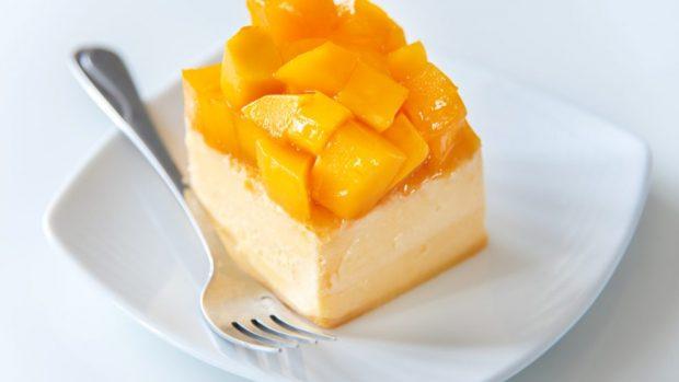 Plato blanco con tenedor de metal con tarta de queso fresco con mango