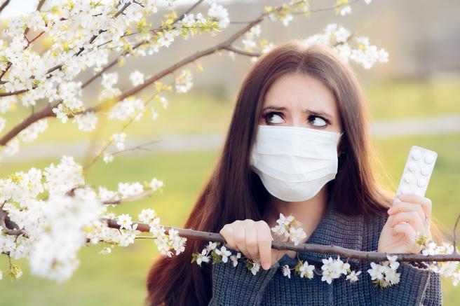 Mujer con mascarilla mriando de reojo a un árbol que le provoca alergia