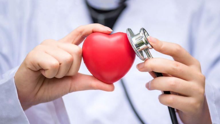 Persona con bata blnaca controlando tensión a un corazón