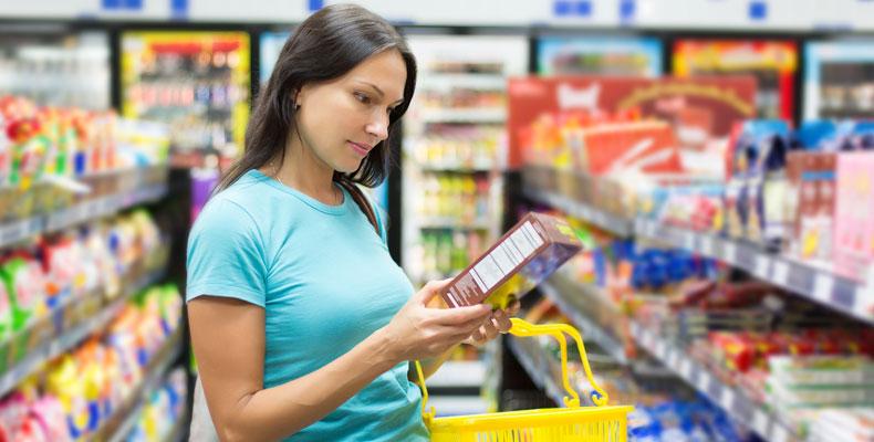 Mujer en el supermercado leyendo las etiquetas de los alimentos