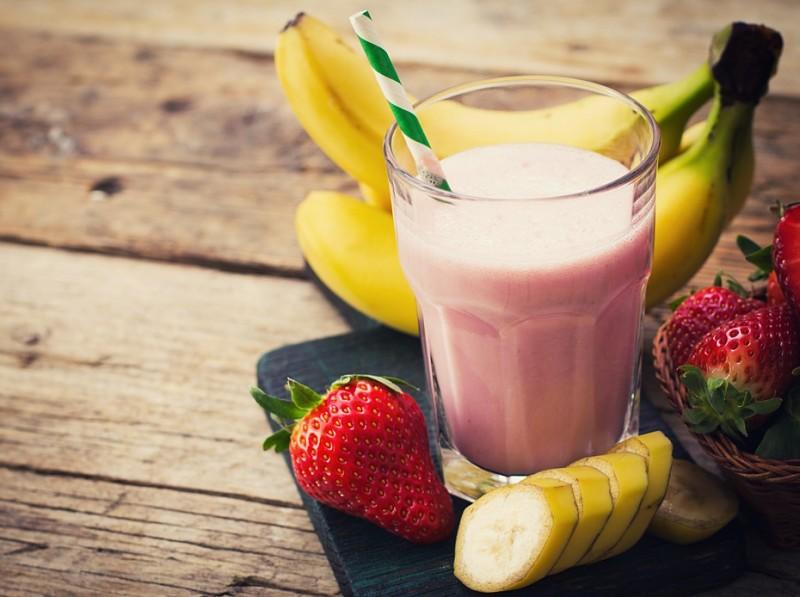 Smoothie de fresa de platano en vaso de cristal con fresas y plátano alrededor