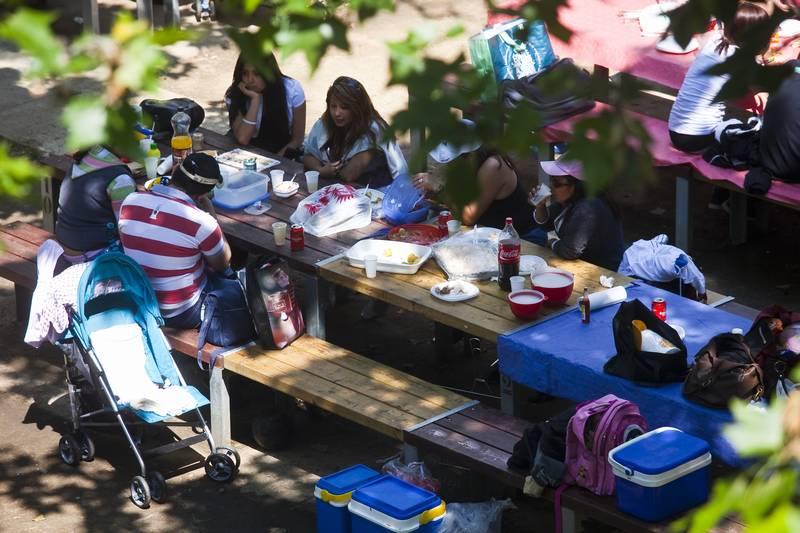 Familia reunida en un banco al aire libre comiendo