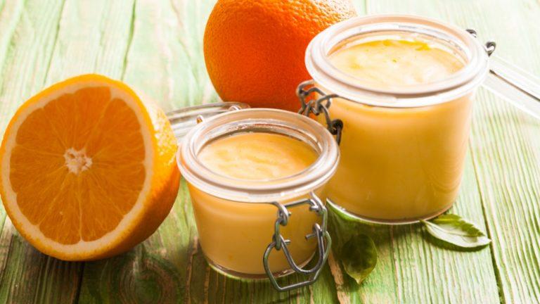 Vasos de cristal con crema de naranja y naranjas alrededor
