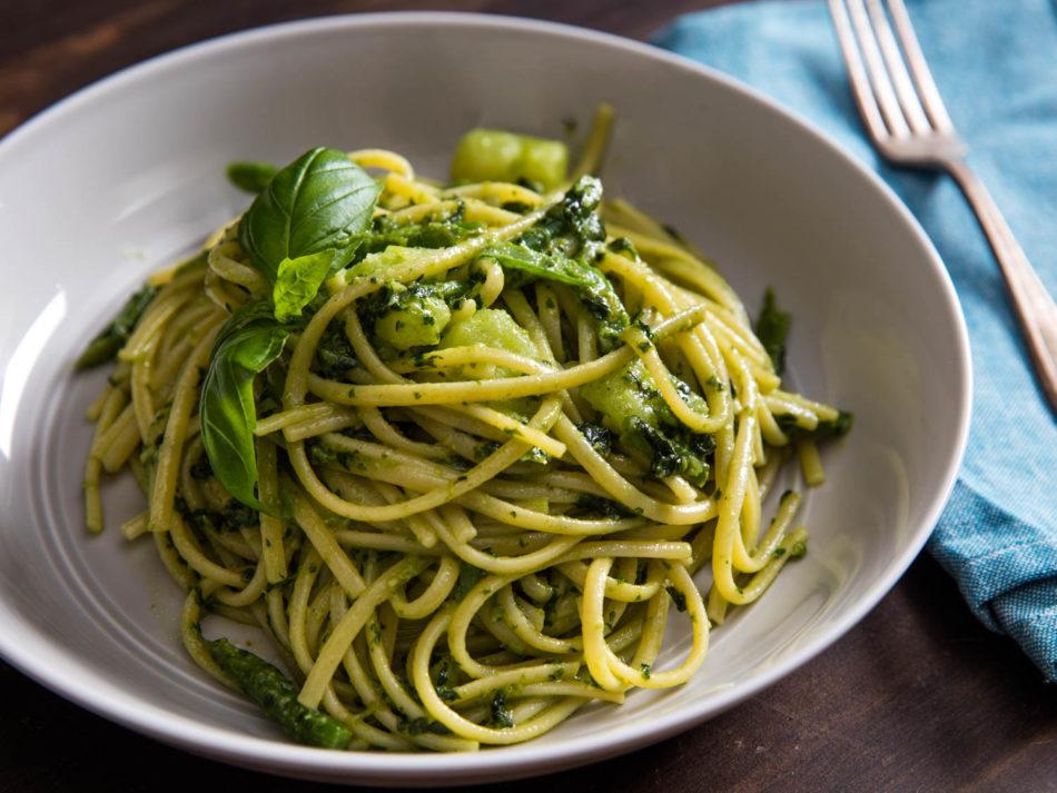 Plato blanco con espaguetis con pesto de perejil y avellanas