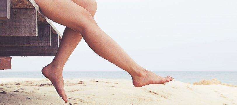Mujer en el borde la playa con las piernas colgando