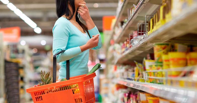 Mujer dudando frente a la balda del supermercado