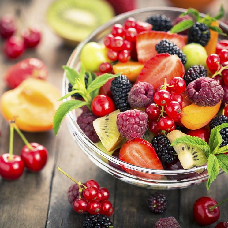 Bol de cristal con frutas de verano como cerezas, piña, cerezas, fresas...