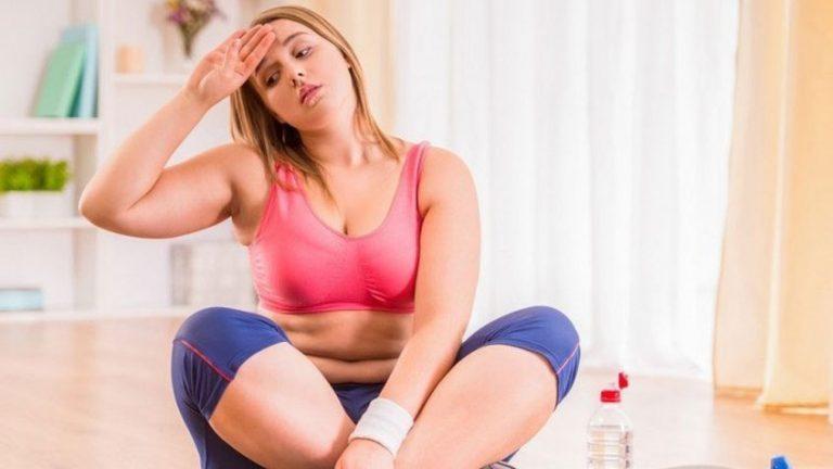Mujer sentada en el suelo cansada de hacer deporte
