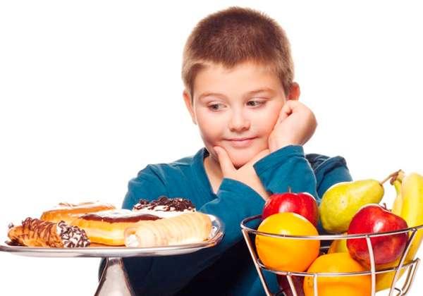 Niño mirando con deseo bollería y en otro lado fruta