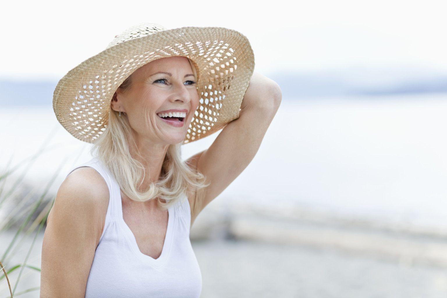 Mujer madura sonriendo en la playa