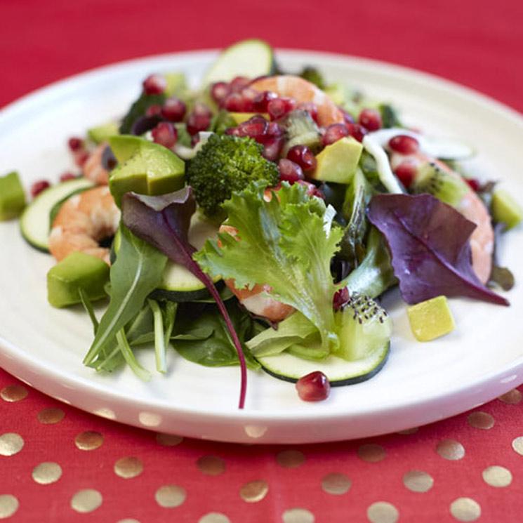 Ensalada de granada, aguacate y langostinos sobre plato blanco encima de mesa con mantel rojo a puntos blancos