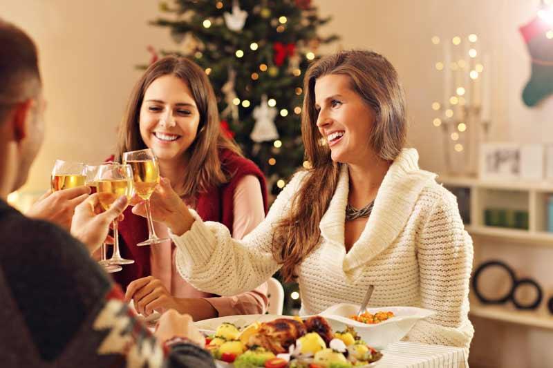 Mujeres brindando y comiendo en mesa de navidad