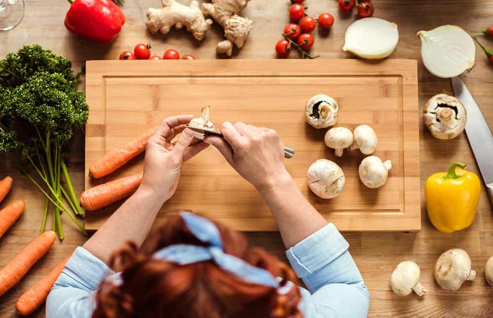 Mujer en la cocina preparanco alimentos sobre tabla de cortar de madera