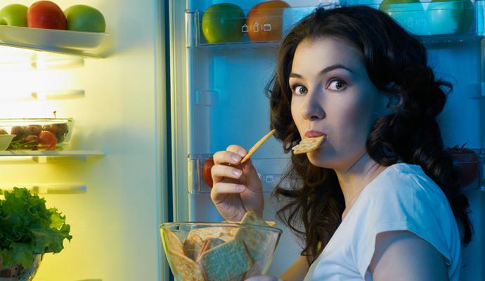 Mujer comiendo galletas con la nevera abierta