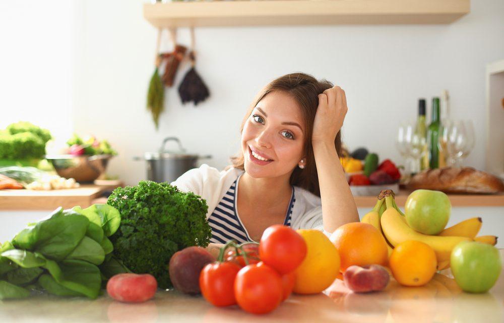 Mujer frente a mesa de la cocina con alimentos saludables