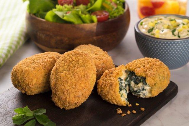 Tabla de pizarra con croquetas de espinacas y queso encima y ensalada y salsa de fondo