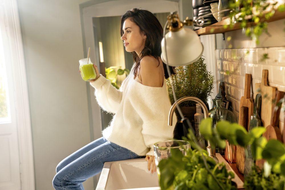 Mujer sentada en la cocina con un batido verde en la mano