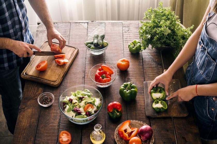 Pareja sobre mesa de madera cortando alimentos