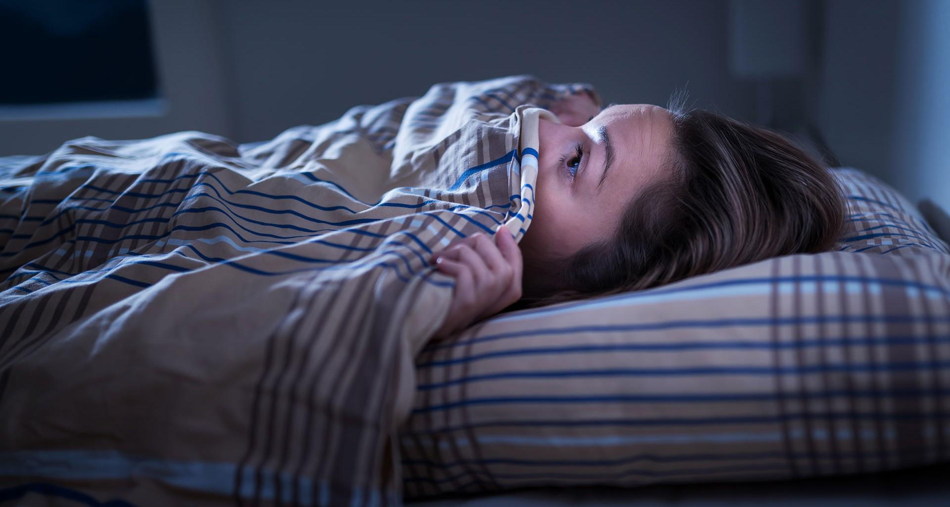 Mujer tapándose la cara en la cama con la sábana