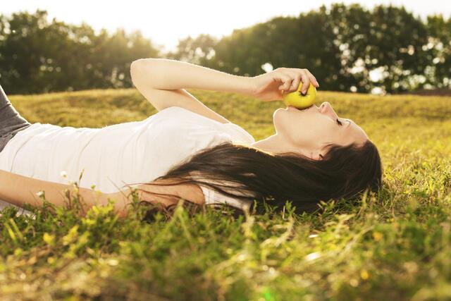 Mujer tumbada en un jardín comiendo una manzana