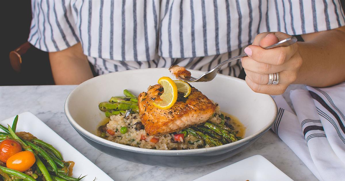 Persona comiendo salmón y verduras sentada a la mesa