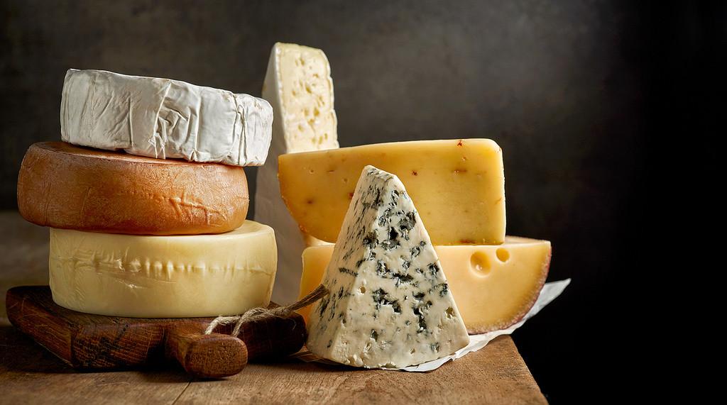 quesos para intolerantes a lactosa sobre mesa de madera