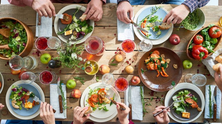 Mesa de madera y ncima platos con alimentos muy variados