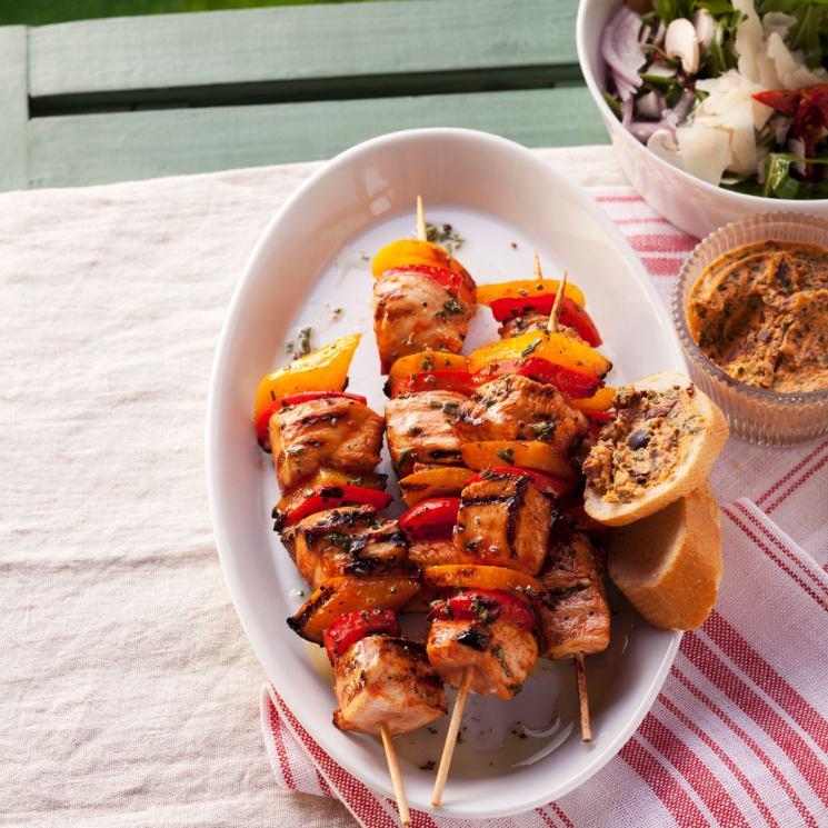Brochetas de pollo con pimiento rojo en plto blanco sobre mesa con mantel a rayas blancas y rosas